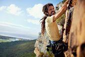 picture of harness  - A rock climbing man with dreadlocks smiling at the camera while climbing up a steep mountain with a harness - JPG