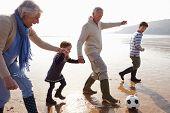 stock photo of grandparent child  - Grandparents With Grandchildren Playing Football On Beach - JPG