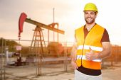 stock photo of  rig  - Refinery worker standing in front of the oil pump - JPG