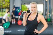 picture of kettlebell  - Portrait of happy female athlete lifting kettlebell at gym - JPG