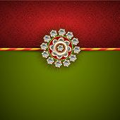 pic of rakhi  - Beautiful white pearl decorated Rakhi on maroon and green background for Raksha Bandhan festival celebrations - JPG