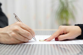 stock photo of divorce-papers  - husband signing divorce agreement and woman push away weeding ring - JPG