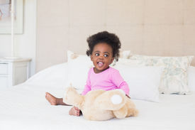 image of babygro  - Baby girl in pink babygro sitting on bed at home in the bedroom - JPG