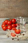 foto of ouzo  - Glasses of ouzo and tomatoes on wooden table - JPG