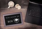 stock photo of thinking outside box  - Tablet touch computer gadget on wooden table think outside the box vintage look - JPG