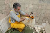 stock photo of chisel  - Adult worker remove demolish old tiles in a bathroom with hammer and chisel - JPG