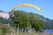 pic of annecy  - paraglider landing by the shore of Lake Annecy