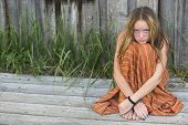 stock photo of hippy  - Young hippie girl sitting on the ground outdoors - JPG