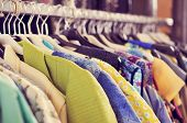 stock photo of racks  - some used clothes hanging on a rack in a flea market - JPG