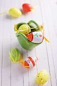 stock photo of paint pot  - Colorful easter eggs in pot on white painted wooden planks - JPG