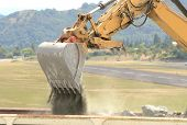stock photo of track-hoe  - A large tracked hoe or excavator working at a construction site to extend an airport runway - JPG