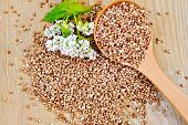 image of buckwheat  - Buckwheat with a flower buckwheat and a spoon on a wooden boards background - JPG