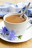 foto of chicory  - Chicory drink in a white cup with a flower and a spoon - JPG