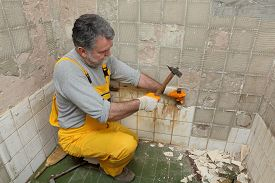 image of chisel  - Adult worker remove demolish old tiles in a bathroom with hammer and chisel - JPG
