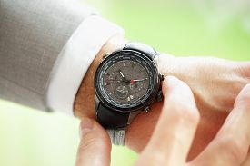 pic of running-late  - Businessman checking the time on his wrist watch concept for urgency - JPG