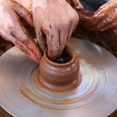 image of molding clay  - Hands working with clay on pottery wheel - JPG