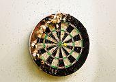 stock photo of bullseye  - Old dart board with yellow dart in bullseye - JPG