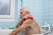 picture of bath sponge  - Senior man washing his body with soap sponge in bath - JPG