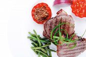 stock photo of sweet pea  - grilled meat beef steaks strips on white plate with sweet pea and tomatoes isolated over white background - JPG