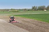 stock photo of plow  - Rural landscape of tractor plowing fertile land near the village - JPG