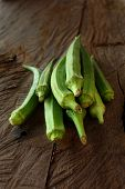 stock photo of okras  - A pile of green Okra on vintage wooden table - JPG