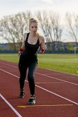stock photo of track field  - Young woman running at a track and field stadium - JPG
