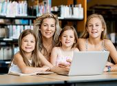pic of mums  - Little girls and their mum with a laptop in library - JPG