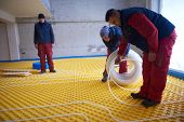 pic of convection  - grouo of workera installing underfloor heating and colling in modern home - JPG