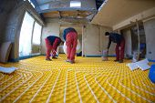 stock photo of convection  - grouo of workera installing underfloor heating and colling in modern home - JPG