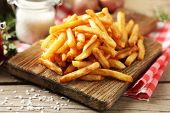 picture of cutting board  - Tasty french fries on cutting board - JPG