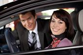 stock photo of showrooms  - Portrait of young couple sitting in a new car at showroom - JPG