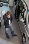 picture of showrooms  - Young man examining new car at showroom - JPG