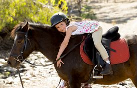stock photo of year horse  - sweet beautiful young girl 7 or 8 years old riding pony horse hugging and smiling happy wearing safety jockey helmet posing outdoors on countryside in summer holiday - JPG