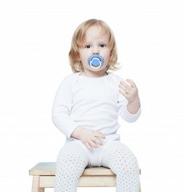 stock photo of pacifier  - little girl with long hair and a pacifier pacifier sitting on a stool - JPG