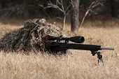 image of prone  - man in a ghille suit holding a rifle looks like a sniper - JPG