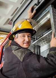 stock photo of firemen  - Portrait of confident mature fireman climbing truck at fire station - JPG