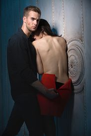 stock photo of jeans skirt  - Young lovers embrace standing near the wall in a beautiful interior - JPG