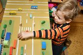 stock photo of nursery school child  - child play in kindergarten street car toys - JPG