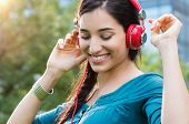 Closeup shot of young woman listening to music in a park. Portrait of happy smiling girl feeling fre poster