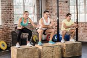 Fit people doing jump box in crossfit gym poster