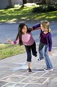 picture of hopscotch  - Multiracial friends having fun playing hopscotch on driveway - JPG