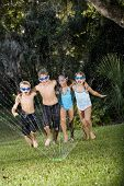 image of sprinkler  - Four happy kids running arm in arm shouting and laughing soaked by lawn sprinkler - JPG