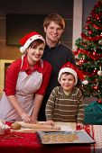 stock photo of nuclear family  - Happy parents with small child baking christmas cake together smiling at camera - JPG