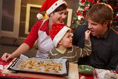 pic of nuclear family  - Small son helping dad tasting christmas cake at table mother watching laughing - JPG