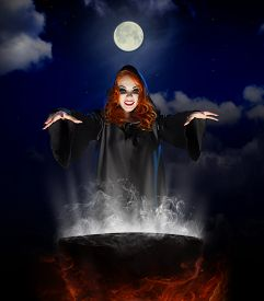 stock photo of cauldron  - Young witch with cauldron on night sky background - JPG
