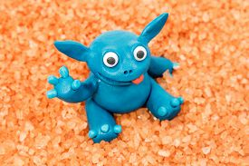foto of creatures  - Blue plasticine creature with a red tongue on the orange granules - JPG