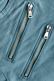 pic of zipper  - Two zippers on blue jeans as a background - JPG