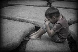 foto of pray  - Young Asian child sitting praying on rocks - JPG