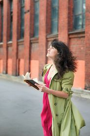 picture of flutter  - young beautiful woman with hair fluttering in the wind in a green coat with old book on background of vintage industrial landscape - JPG