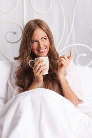 image of flirty  - Beautiful Flirty Woman Drinking hot tea In The Bed - JPG
